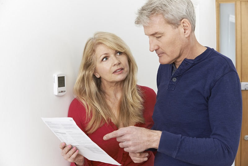 senior couple with heating bill turning down thermostat