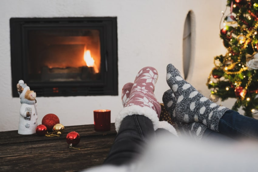 Two people with their feet up beside a gas fireplace