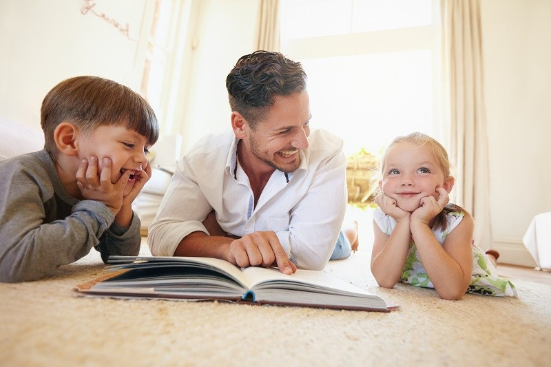 father-two-kids-indoors-smiling-reading-sunshine