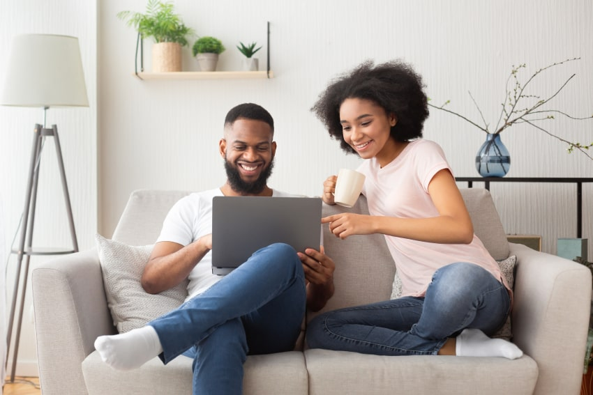 Couple on laptop researching air purifier vs humidifier