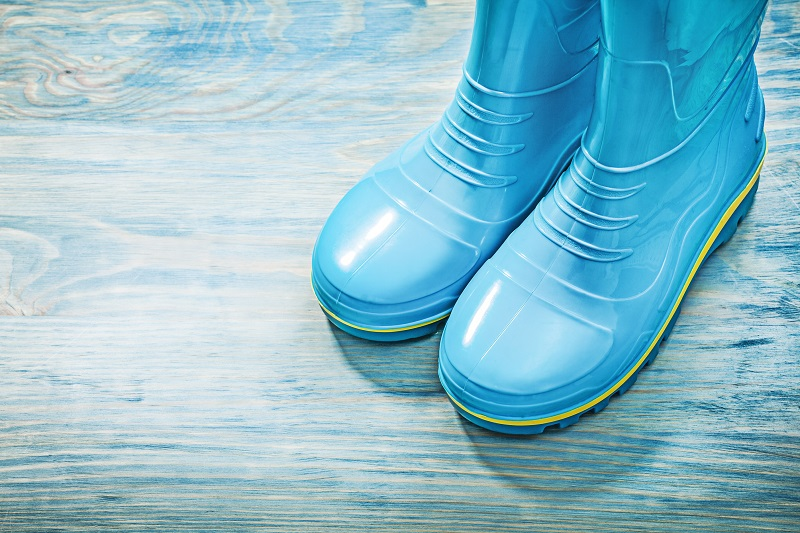 blue-rubber-boots-on-wooden-board