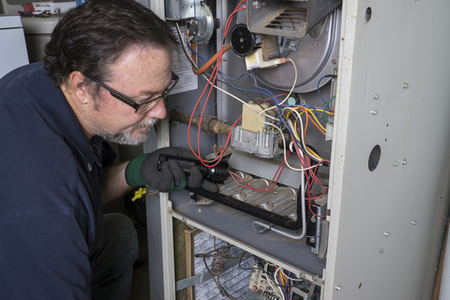 Technician Working on a Furnace Tune Up