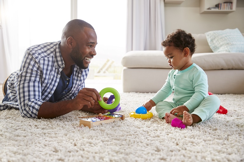 black-man-playing-on-floor-of-home-with-toddler